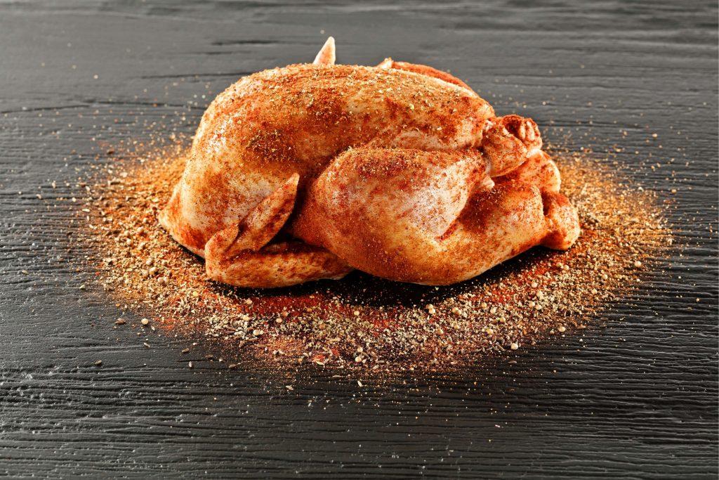 Assaisonner le poulet à l'intérieur et extérieur avant de le placer dans le barbecue.